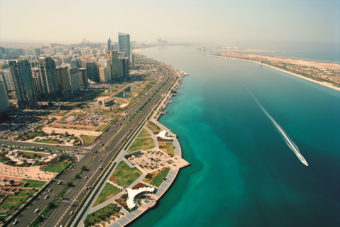 Aerial view over Abu Dhabi's vibrant city and the Corniche (waterfront area).